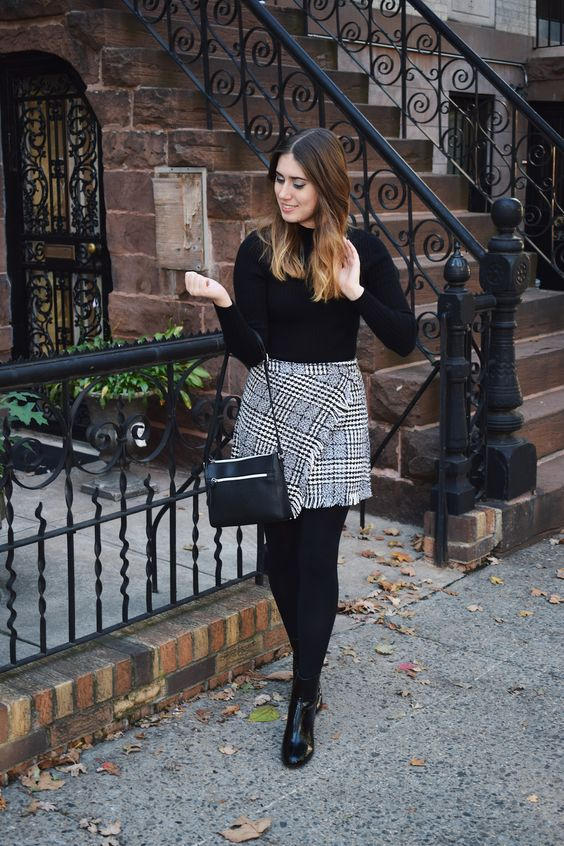 a black turtleneck, a grey tweed wrap mini skirt, black booties and stockings plus a black bag
