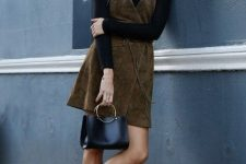 a black turtleneck, a slate green suede overall, black booties and a black bag for a chic look