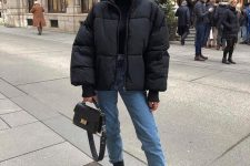 a black turtleneck, an oversized black puffer jacket, blue jeans, black Chelsea boots and a black bag