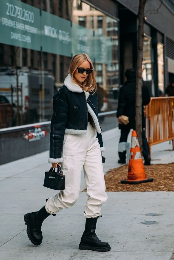 a black turtleneck, white cargo pants, black Chelsea boots, a denim jacket with a small bag