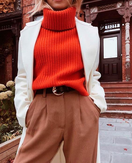 a bold and vivacious look with an orange chunky knit sweater, brown pants, a creamy midi coat and a brown belt
