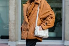 a bold look with a cognac leather puff coat, black trousers, cognac chelsea boots and a white woven bag