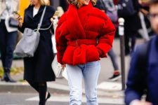 a bold winter look with light blue jeans, bright sporty trainers, a red puffer jacket with a belt