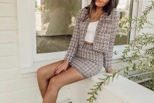 a brown and white tweed suit with a cropped blazer, a mini skirt, a cropped white top and white trainers