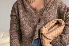 a brown knit top and a matching cardigan with pockets, blue jeans and a woven beige bag plus layered necklaces