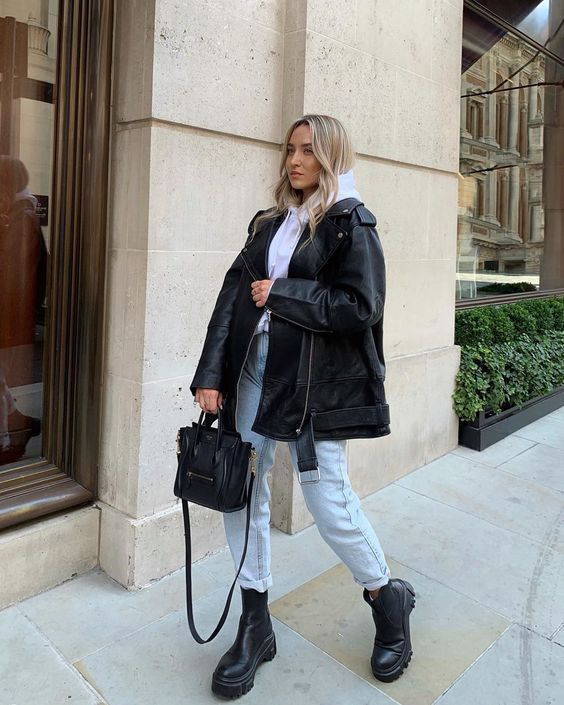 a casual winter look with a white hoodie, light blue jeans, black Chelsea boots, a black leather jacket and a bag