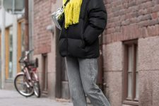 a casual yet bold winter look with a black puff jacket, grey jeans, white Chelsea boots and a lemon yellow scarf