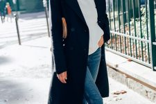 a chic look with a black top, a white cashmere hoodie, blue skinnies, snakeskin print boots, a black coat wows