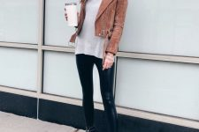 a chic look with an oversized grey sweater, black leather leggings, boots and an ocher suede moto jacket