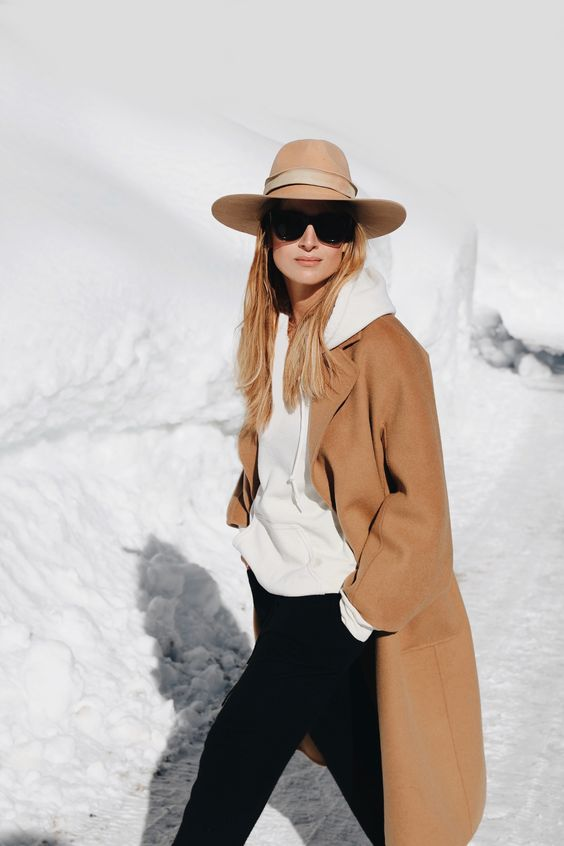 a chic outfit with a white cashmere hoodie, black skinnies, a tan coat and a tan hat