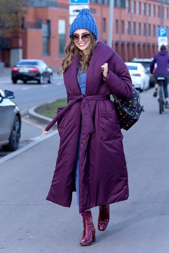 a colorful winter look with a blue jumper and jeans, fuchsia lacquer boots, a purple puffer coat with a belt and a blue beanie
