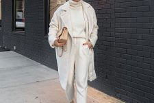 a comfortable everyday look with a white sweater, white joggers, sneakers, a fau fur coat and a tan bag