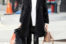 a comfortable winter look with black leather leggings, an oversized white sweater, grey trainers, a faux fur coat and a tan bag
