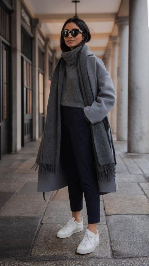 a comfy casual look with a grey turtleneck sweater, navy striped pants, white sneakers, a grey scarf and a grey coat
