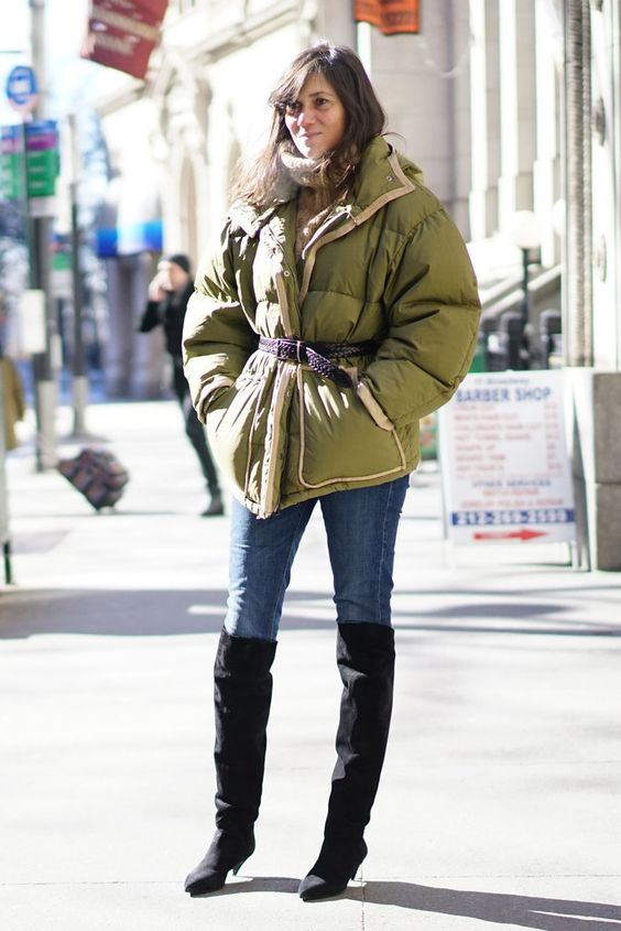 a comfy winter look with a tan sweater, blue jeans, black tall boots with kitten heels, a green puffer jacket with a belt