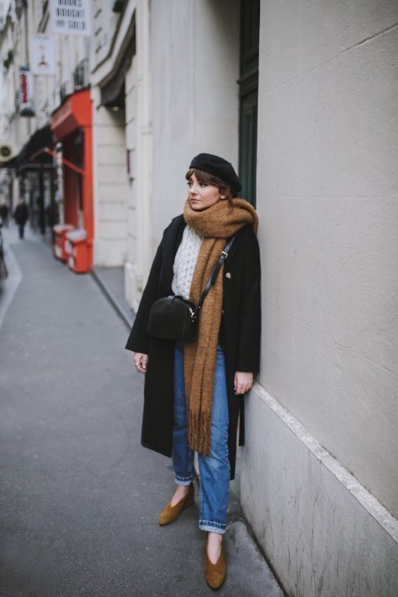 a cozy winter look with a white chunky sweater, blue jeans, a black coat and a beret, a crossbody bag, mustard shoes and an oversized tan scarf
