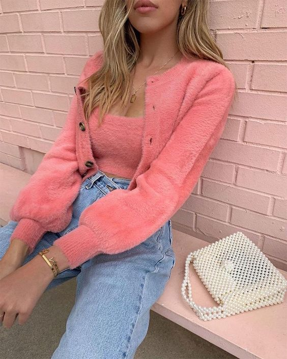 a cute girlish look with a pink fluffy tank top and a cardigan, blue jeans and a white pearled bag is whimsy