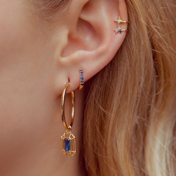 a gold hoop earring with a sapphire, a small sapphire earring and some matching cuffs