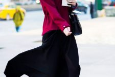 a gorgeous look with a fuchsia warm hoodie, a black asymmetrical midi skirt, black booties and a black bag
