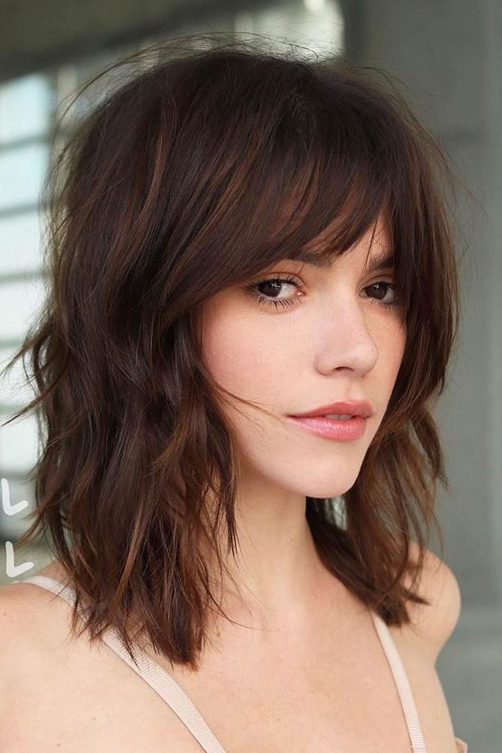 a gorgeous shaggy and wavy dark chestnut long bob with a 70s inspired curtain fringe