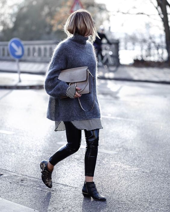 a graphite grey turtleneck oversized sweater, a long striped shirt, shiny black leather leggings, black booties and a large grey clutch