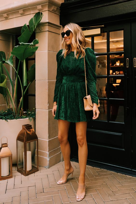 a green velvet fitting mini dress with puff sleeves, a tan bag and sheer heels for a party
