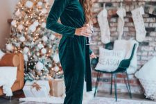 a green velvet jumpsuit paired with metallic heels and with statement earrings looks amazing