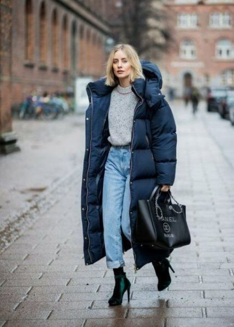 a grey chunky sweater, blue jeans, emerald velvet boots, a navy midi puffer coat and an oversized black bag