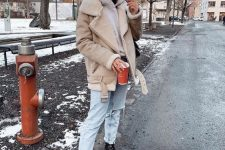 a grey hoodie, a tan and white shearling coat, light blue jeans, black boots and a black bag