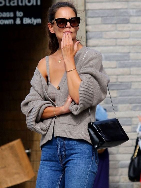 a grey knit cardigan and a matching crop top, blue jeans and a black bag make up a cozy and comfy look