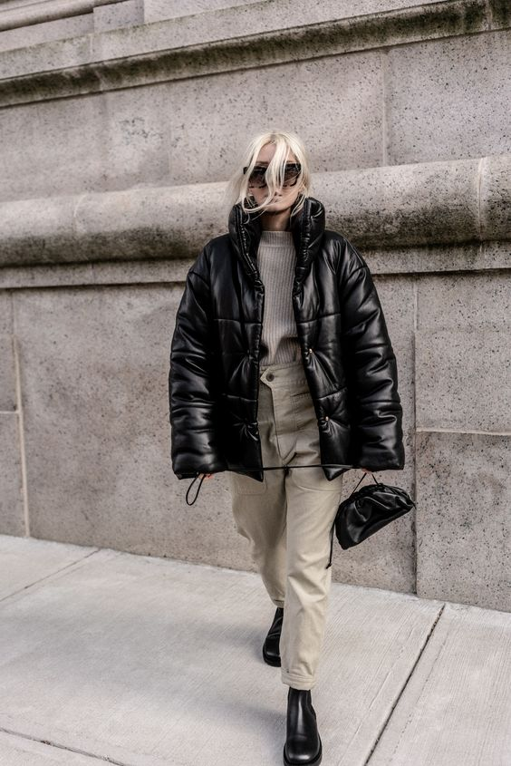 a grey sweater, neutral cargo pants, black Chelsea boots, a black bag and a black leather puffer jacket