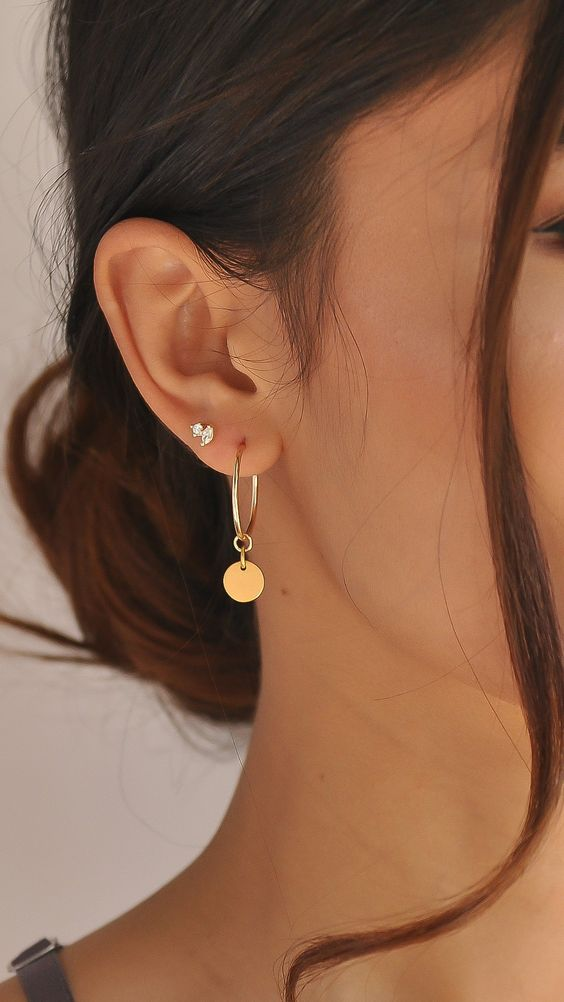 a large gold hoop earring with a coin hanging on it and a tiny embellished stud look chic together