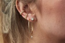a large hoop earring with a rhinestone, a shiny stud, gold embellished cuffs for an ultra-modern look