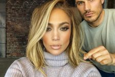 a long shaggy bob with blonde balayage and a long side fringe by J.Lo