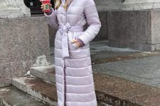 a lovely pastel look with white pants, blush boots, a lilac puffer coat with a belt and a white beanie