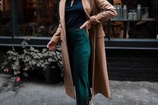 a navy turtleneck, emerald cropped pants, white trainers and a camel midi coat compose a lovely and comfy look