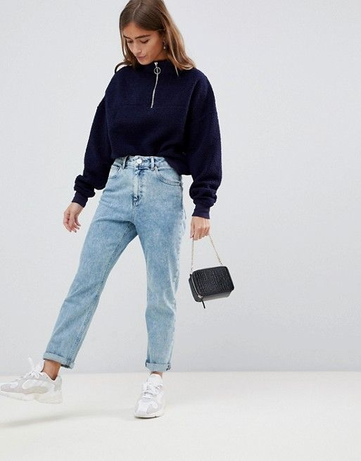 a navy zip sweater, light blue jeans, grey trainers, a small black bag for a fall or winter look