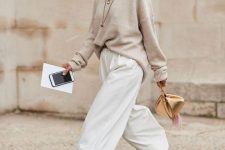 a neutral oversized sweater, white wideleg pants, tan and black boots and a gold bag – add a coat and go