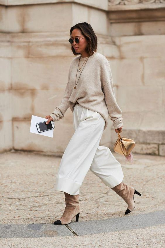 a neutral oversized sweater, white wideleg pants, tan and black boots and a gold bag   add a coat and go