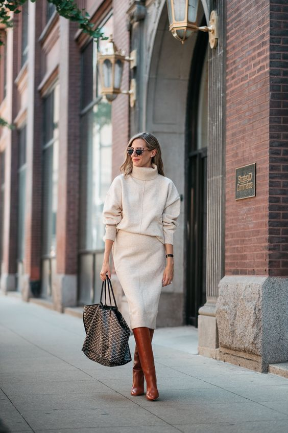 a neutral turtleneck sweater and a matching pencil midi skirt, cognac wide boots and a large printed bag