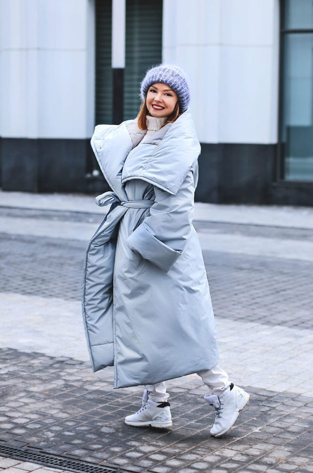 a pastel and neutral look with a white sweater, white jeans, trainers, a powder blue puffer coat with a belt and a blue beanie