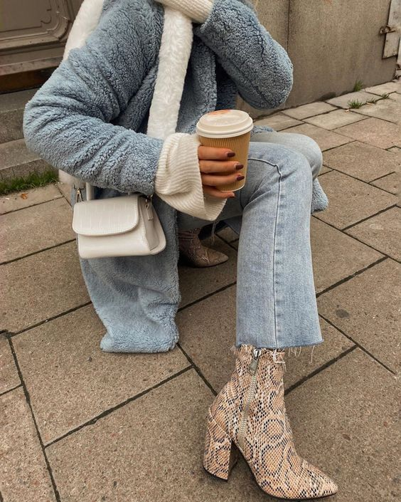 a powder blue faux fur jacket, matching jeans, snakeskin booties and a white bag on a fur strap
