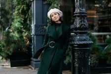a refined look with a dark green midi dress and a matching coat, dark green velvet boots and a white beret