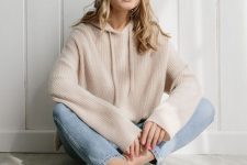a relaxed and girlish outfit with a blush cashmere hoodie, light blue jeans, taupe mules is ideal