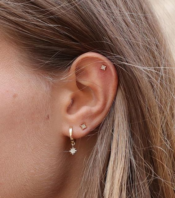 a silver hoop earring with a tiny star pendant and matching star studs all over the ear
