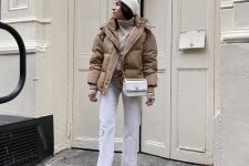 a simple and comfortable winter look with a white sweater, jeans, hiking boots, a tan leather puffer jacket and a white beanie and bag