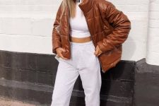 a simple look with a white crop top, joggers, an amber leather puffer jacket and white trainers for every day