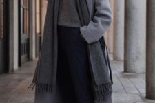 a simple outfit with an oversized grey turtleneck sweater, navy thin striped pants, white sneakers, a midi coat and a scarf
