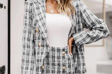 a skirt suit with a blazer and a mini, gold buttons, a white bag, cap and a top plus layered necklaces for a catchy work look