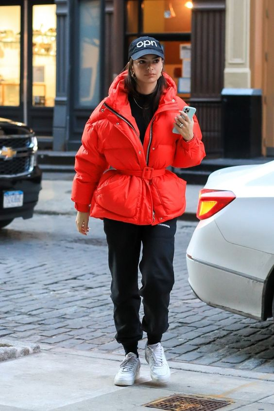 a sporty winter look with a black turtleneck, joggers, white trainers, a red puffer jacket with a belt and cap